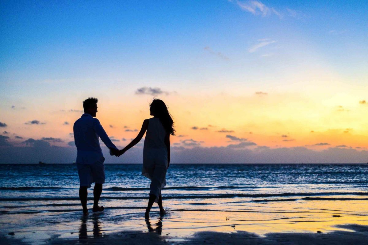 man and woman walking on the beach at sunset