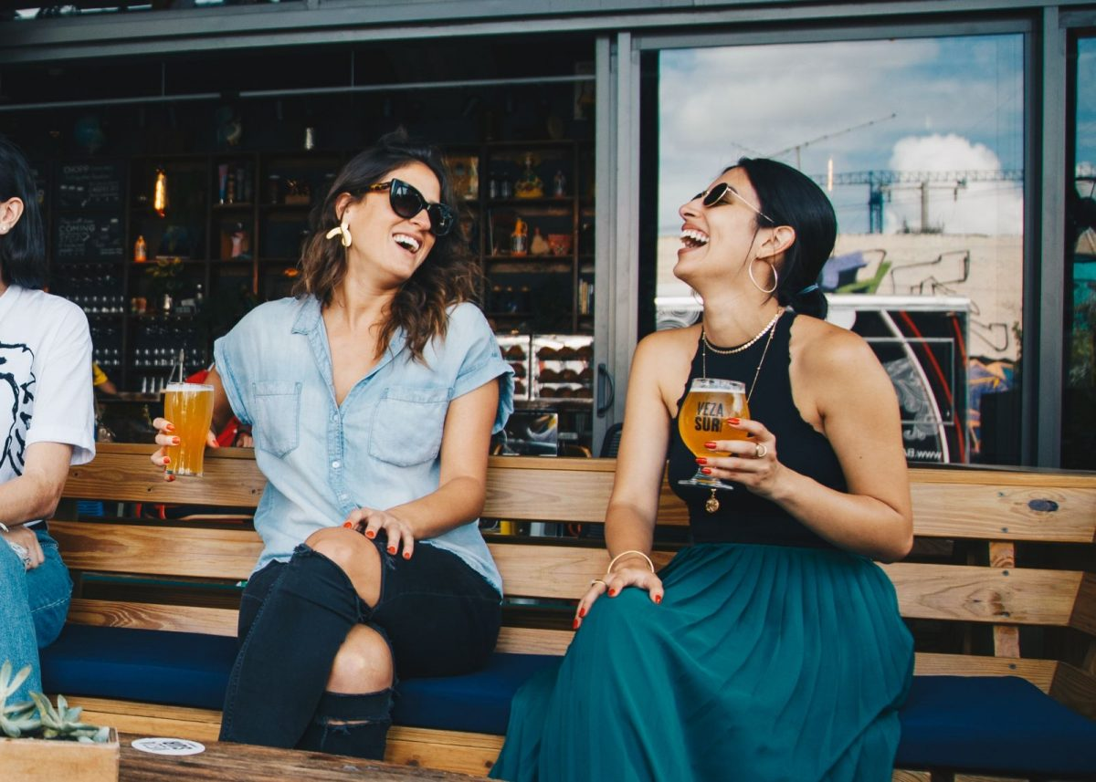 two woman laughing on a bench