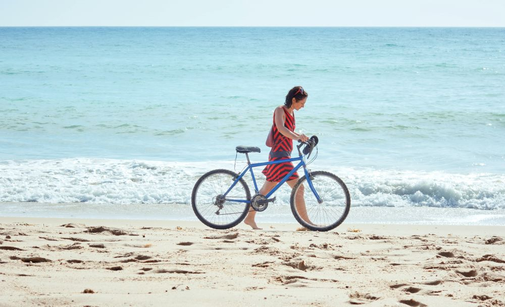 woman walking bike on the beach
